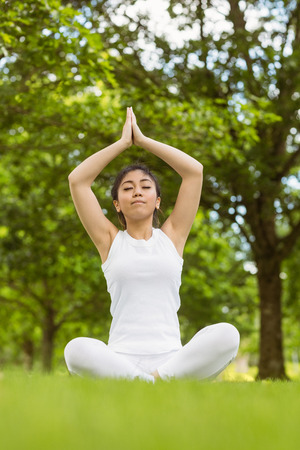 joined hands: Full length of healthy and beautiful young woman sitting with joined hands at park Stock Photo