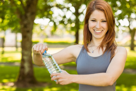 Pretty redhead opening bottle of water on a sunny day Stock Photo