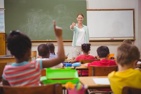 escuela primaria: Los alumnos que levantan sus manos durante la clase en la escuela primaria Foto de archivo