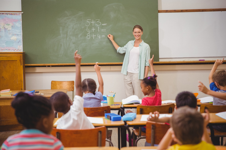 early childhood education: Pupils raising their hands during class at the elementary school Stock Photo