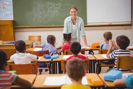maestro: Pretty profesor hablando con los j�venes alumnos en el aula en la escuela primaria