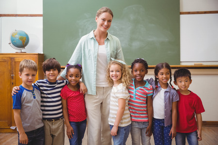 teaching adult: Cute pupils smiling at camera in classroom at the elementary school
