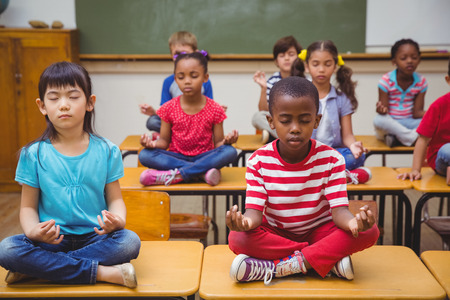classroom: Pupils meditating in lotus position on desk in classroom at the elementary school
