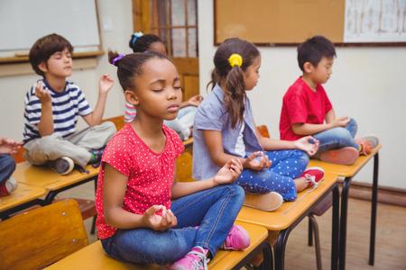 kinderschoenen: Leerlingen mediteren in lotushouding op het bureau in de klas op de basisschool