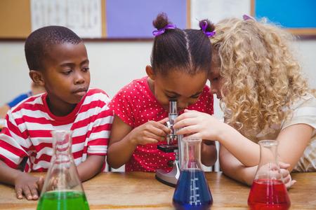 かわいい生徒の小学校における顕微鏡を通して見る