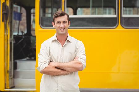 bus driver: Sonre�r conductor del autob�s de pie con los brazos cruzados frente a su autob�s