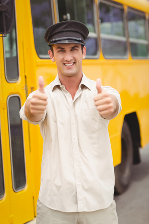 bus driver: Sonre�r conductor del autob�s mirando la c�mara fuera de la escuela primaria Foto de archivo