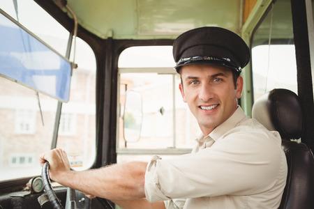 chofer de autobus: Conductor Sonre�r conducir el autob�s escolar fuera de la escuela primaria