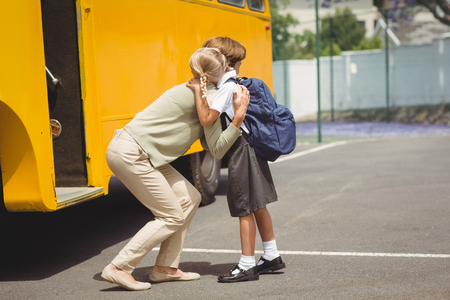 first day of school: Mother hugging her daughter by school bus outside the elementary school