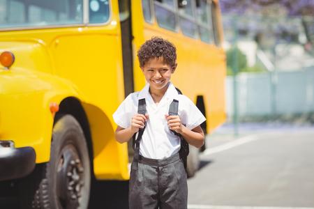 autobus escolar: Sonriendo a la cámara por el autobús escolar fuera de la escuela primaria lindo alumno