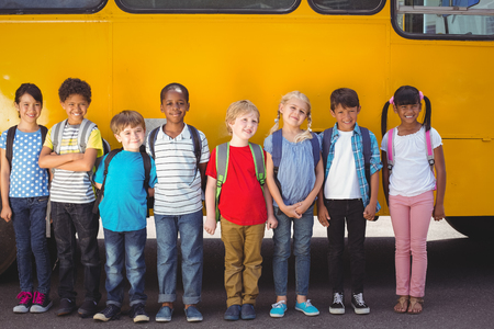 Cute pupils smiling at camera by the school bus outside the elementary school Stock Photo