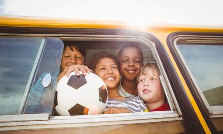 escuela primaria: Alumnos lindos sonriendo a la c�mara en el autob�s escolar fuera de la escuela primaria Foto de archivo