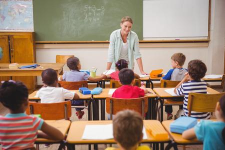 salle de classe: Jolie enseignant � parler aux jeunes �l�ves en salle de classe � l'�cole �l�mentaire Banque d'images