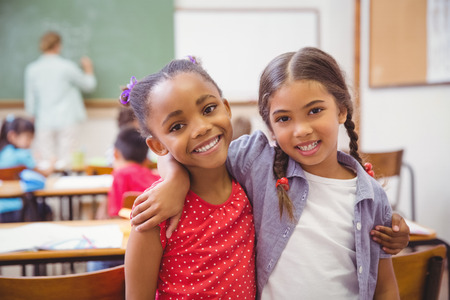asian teacher: Cute pupils smiling at camera in classroom in slow motion Stock Photo