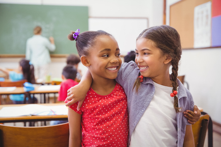 slow motion: Cute pupils smiling at camera in classroom in slow motion Stock Photo