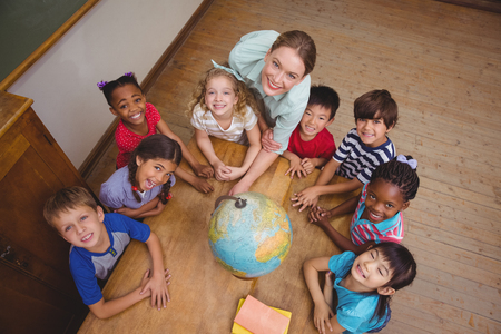 female teacher: Cute pupils smiling around a globe in classroom with teacher at the elementary school