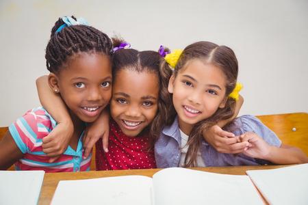 salon de clases: Alumnos lindos sonriendo a la c�mara en el aula en la escuela primaria Foto de archivo