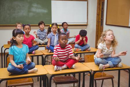 Schüler Meditation im Lotussitz auf dem Schreibtisch im Klassenzimmer in der Grundschule