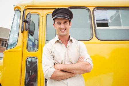 conductor autobus: Sonre�r conductor del autob�s mirando la c�mara fuera de la escuela primaria Foto de archivo