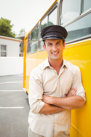 driver cap: Smiling bus driver looking at camera outside the elementary school