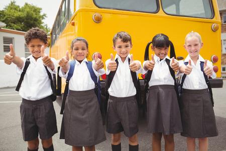 schoolchild: Leuke leerlingen lachend naar de camera door de schoolbus buiten de basisschool Stockfoto