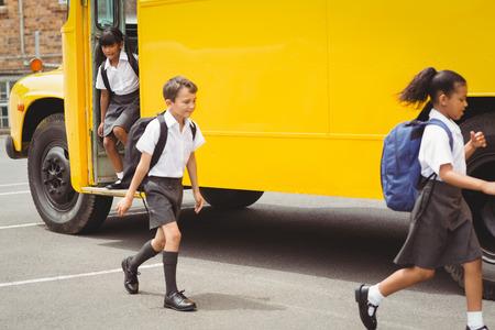 escuela primaria: Lindos escolares bajando del autob�s escolar fuera de la escuela primaria