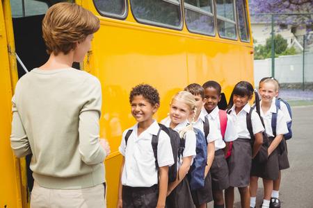 Leuke leerlingen wachten op de schoolbus te krijgen buiten de basisschool Stockfoto