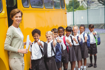 uniforme escolar: Lindos escolares esperando para entrar en el autob�s escolar fuera de la escuela primaria Foto de archivo
