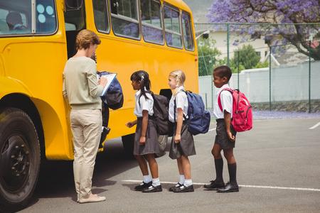 escuela primaria: Lindos escolares esperando para entrar en el autob�s escolar fuera de la escuela primaria Foto de archivo