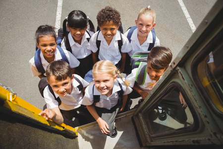schoolchild: Leuke leerlingen krijgen op school bus buiten de basisschool Stockfoto