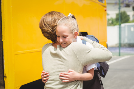 school child: Mother hugging her daughter by school bus outside the elementary school
