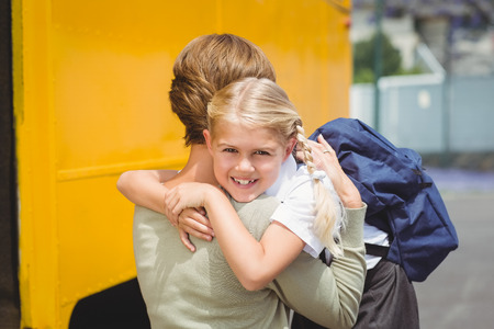 transporte escolar: Madre que abraza a su hija en autob�s escolar fuera de la escuela primaria