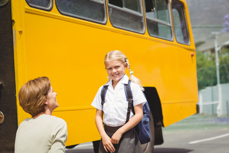 one parent: Mother with her daughter by school bus outside the elementary school Stock Photo