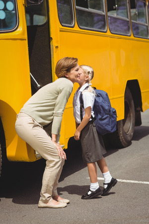 public schools: Mother kissing her daughter by school bus outside the elementary school Stock Photo