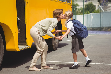 girls kissing girls: Mother kissing her daughter by school bus outside the elementary school Stock Photo