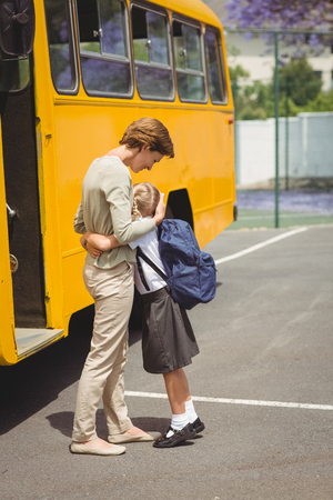 parent child: Mother hugging her daughter by school bus outside the elementary school