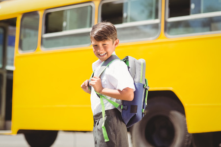 niño escuela: Lindo alumno a pie del autobús escolar fuera de la escuela primaria