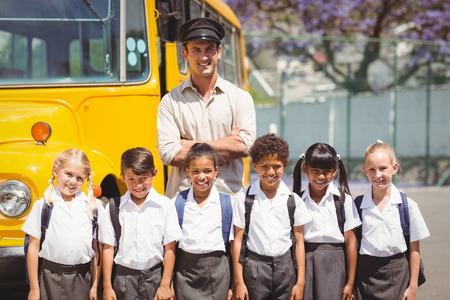 autobus escolar: Alumnos lindos con su conductor del autob�s escolar fuera de la escuela primaria