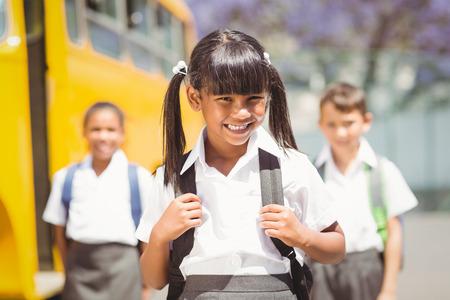 autobus escolar: Sonriendo a la c�mara por el autob�s escolar fuera de la escuela primaria lindo alumno