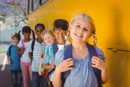 coach bus: Cute pupils smiling at camera by the school bus outside the elementary school Stock Photo