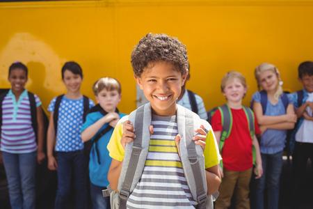 autobus escolar: Alumnos lindos sonriendo a la cámara por el autobús escolar fuera de la escuela primaria Foto de archivo