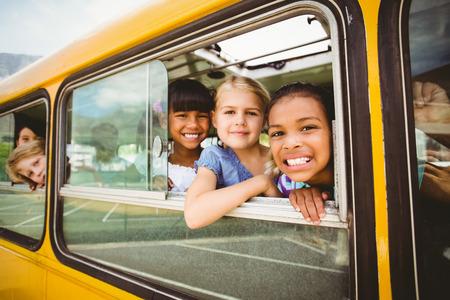 초등학교 밖에 학교 버스에 카메라를 웃는 귀여운 학생 스톡 콘텐츠