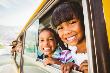viagem: Alunos sorriso bonito na câmera no ônibus escolar fora da escola primária