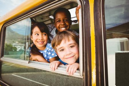 Leuke leerlingen lachend naar de camera in de schoolbus buiten de basisschool