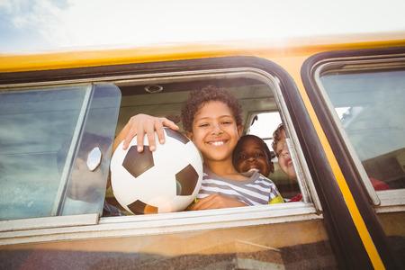 transporte escolar: Alumnos lindos sonriendo a la c�mara en el autob�s escolar fuera de la escuela primaria Foto de archivo