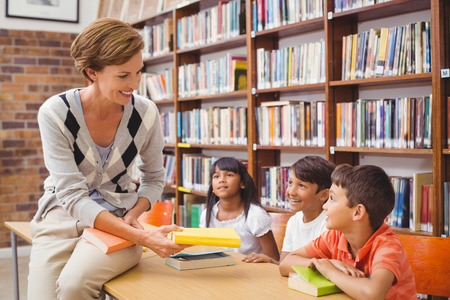 boy book: Cute pupils and teacher looking for books in library at the elementary school Stock Photo