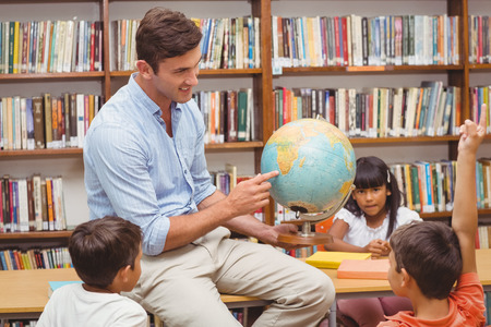 early 30s: Cute pupils and teacher looking at globe in library at the elementary school