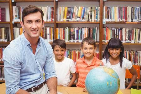 asian teacher: Cute pupils and teacher looking at globe in library at the elementary school