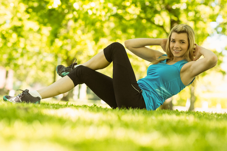 sit up: Fit blonde doing sit ups in the park on a sunny day