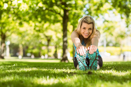 touching toes: Fit blonde stretching on the grass on a sunny day